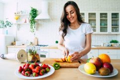 Beautiful woman making fruits smoothies with blender.
